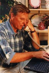 Man on telephone with laptop computer.