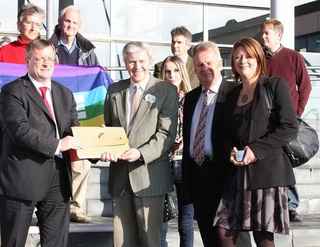 William Powell AM accepting petition from Arfon Jones. Rhodri Glyn Thomas AM and Leanne Wood AM (left to right)